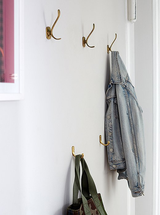 A double row of vintage hooks lets Ari hang her coats above and her totes and bags below.