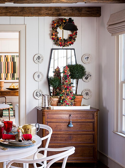 A kitchen corner gets merry with a miniature beaded-fruit tree and matching wreath—both selected to tie into the red, green, and gold scheme.