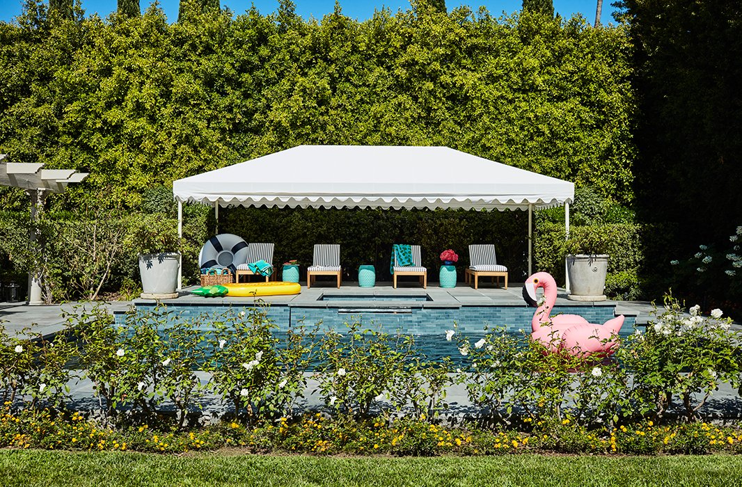Poolside, a striped and scalloped cabana provides shade for a row of loungers. A flamingo by SunnyLife drifts close by.