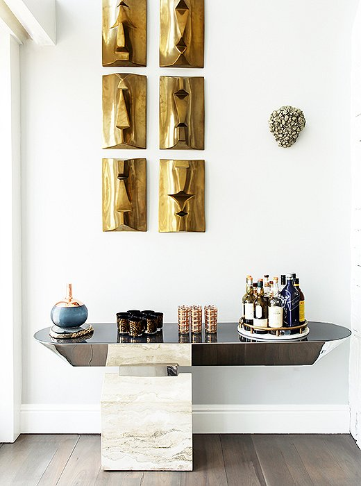 """A marble-and-chrome bar by Brueton merges a man-made metal with an earthy element. Above, six brass-head sculptures with a slight patina offer a high-style touch with a subtle sensibility. Sasha was careful not to overpower the space with too much polish. """"We didn't want it to be too sleek,"""" she says, so it was important to counterbalance anything burnished with something less lustrous."""