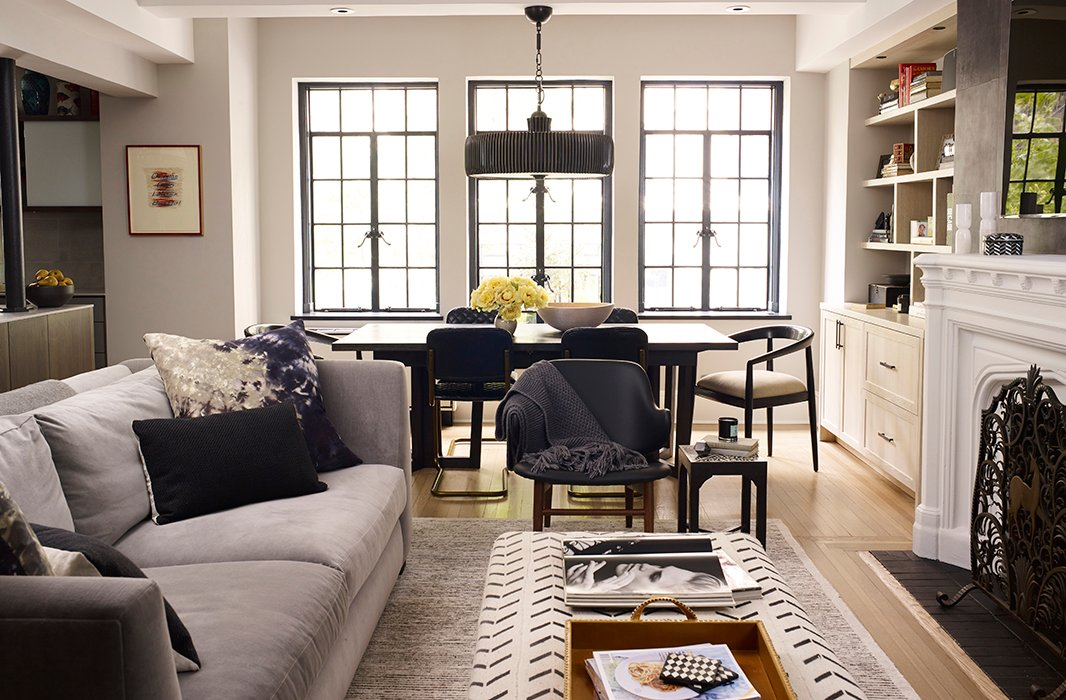The open-plan living, kitchen, and dining area is flooded with light that pours in from the original iron-frame windows (Suki and Morgan worked with architect Pamela Glazer to transform the apartment from a cramped state to the wide open space it is now). A deep-seated sofa in gray velvet is accented with graphic pillows by Kim Salmela and paired with an ottoman by Tammy Price to create an area perfect for lounging (and the occasional afternoon nap).