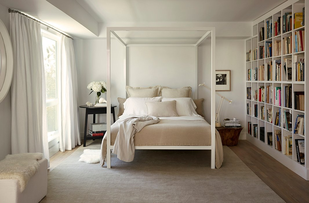 A Tizio lamp separates the canopy bed from a wall of built-ins designed by Foley, with cubbies that make organizing books by category an easy feat. On the floor, a taupe rug bridges the tonal gap between the oak floors and the matte walls (painted in Benjamin Moore's Decorator White).