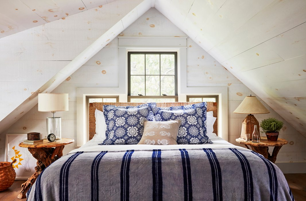 "Nightstands found at the Brimfield Antique Show flank a woven-rush headboard in a cozy guest bedroom. The pine-clad walls were washed with milk paint, which ""added a great textural quality,"" says T.R."