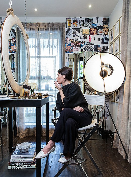 Cassandra takes a moment to touch up her lipstick in the studio. The mirror is from Baker's Bill Sofield Collection, and the designer also created the custom makeup table. The tripod floor lamp is by Mariano Fortuny for Pallucco.
