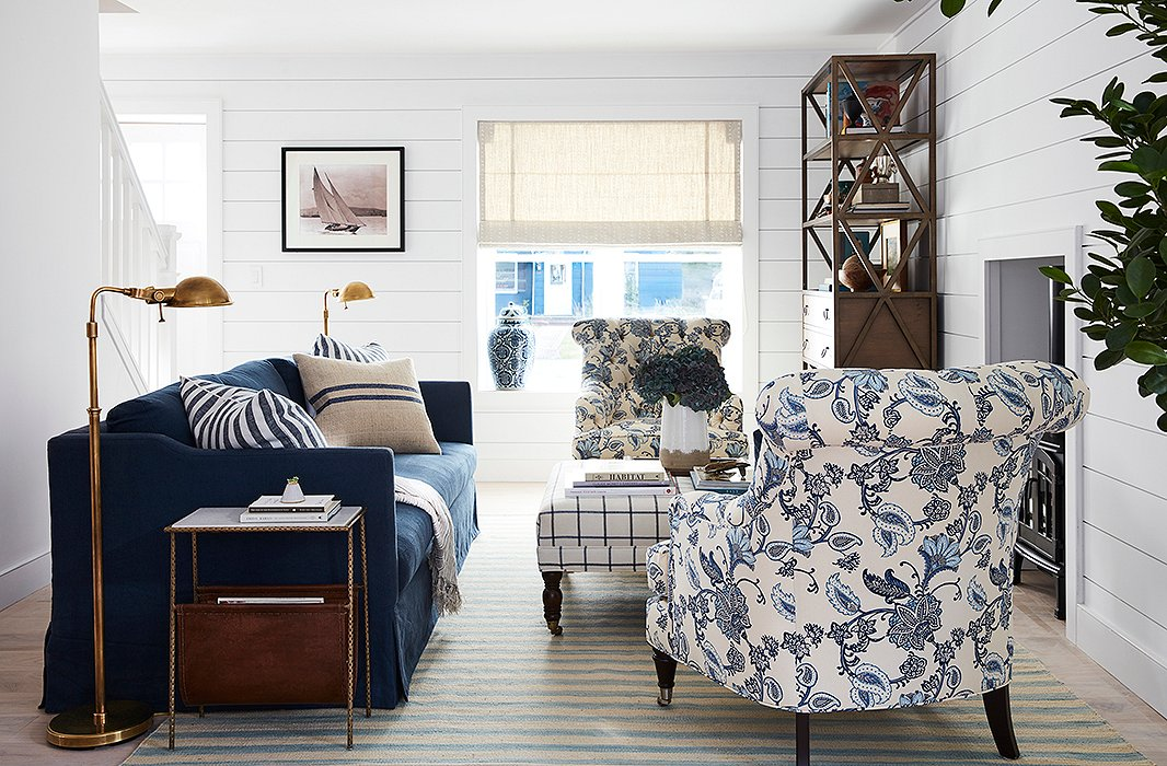 "Brass pharmacy lamps by Ralph Lauren Home flank a Brownstone sofa in indigo linen. ""Will was drawn to very classic yet masculine pieces,"" says Sally. Patterned chairs by Barclay Butera soften the look, and an ottoman by Miles Talbott serves as extra seating when neighbors pop by."