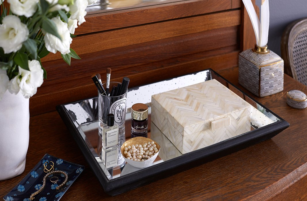 A mirrored tray corrals the candle vessel that holds Ari's makeup and a mini catchall in which she stashes jewelry. The horn box holds other accessories and keepsakes.