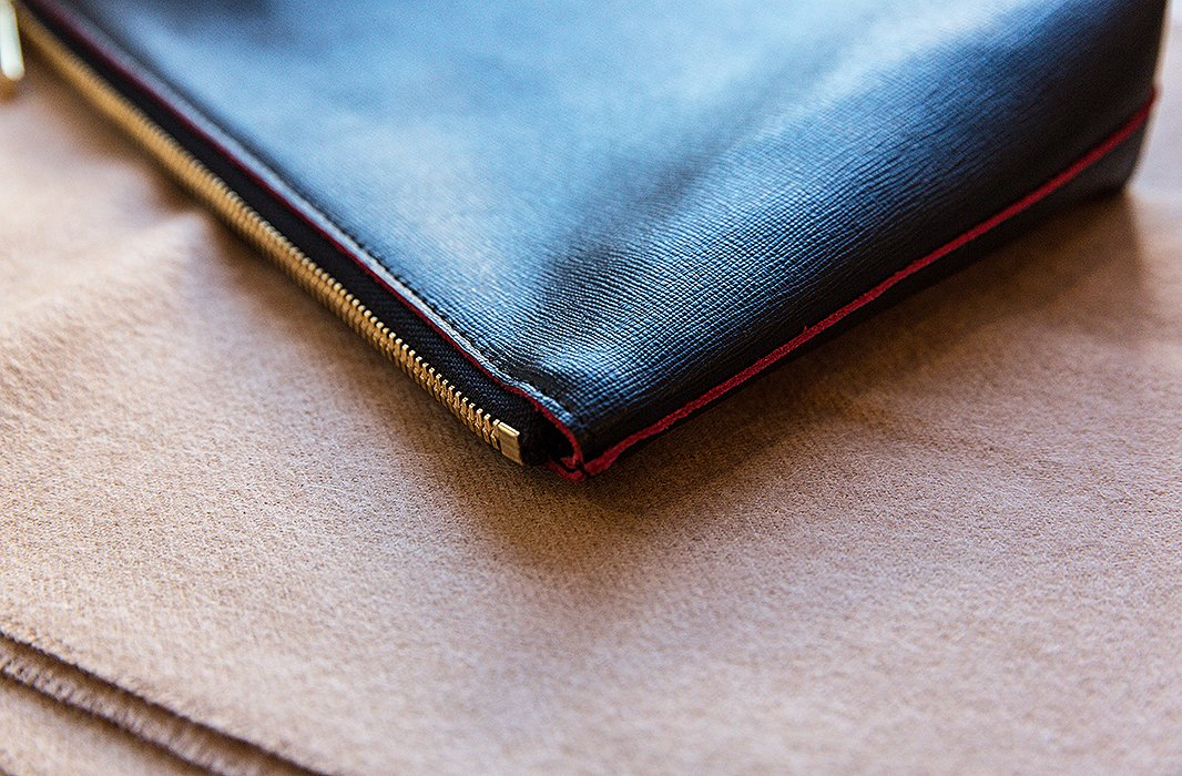 One of the leather pouches against soft camel-tone cashmere.