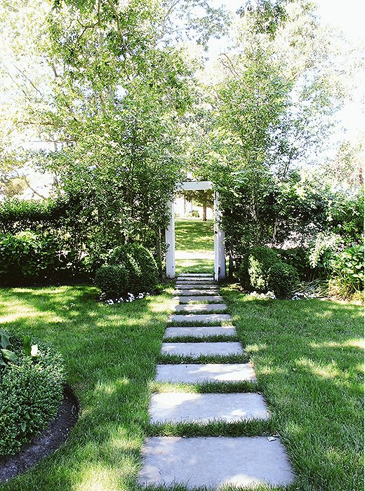 The garden is as charmingly undone as the rest of the home, with boxwood shrubs flanking the entryway and simple stone slabs forming a path through the grass.