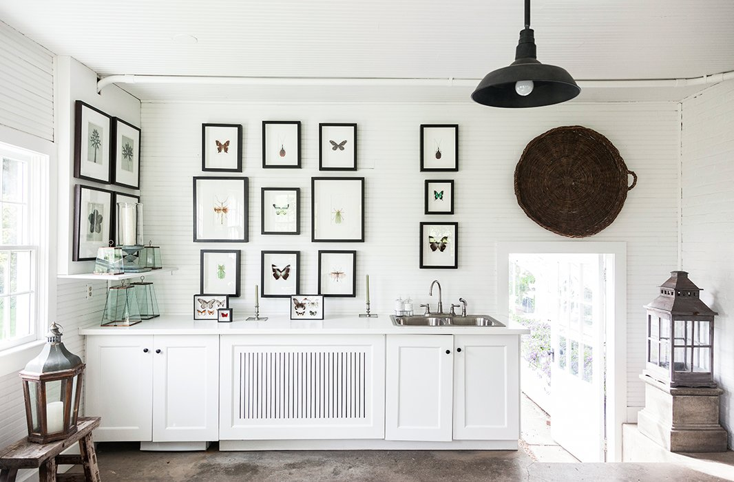 Matching black frames contrast beautifully with this room's stark white walls and cabinetry. Photo byLesley Unruh.