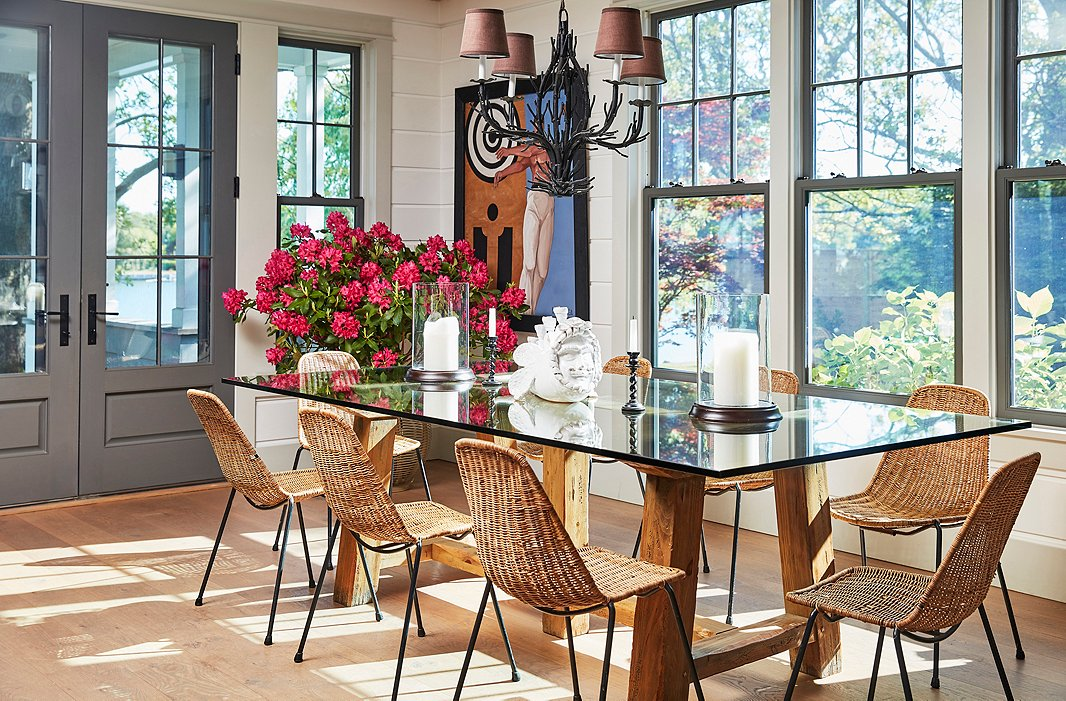A chandelier from Laurin Copen Antiques in Bridgehampton hangs above a dining table crafted of reclaimed wood and glass. The set of midcentury wicker chairs was a lucky find from Paris's Clignancourt flea market.
