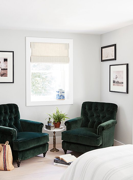 A soothing spot in the bedroom's niche. Black-and-white prints of tennis players hang behind a duo of velvet green armchairs by Miles Talbott. Between them sits a brass side table with a marble top just big enough to hold two cups of coffee.