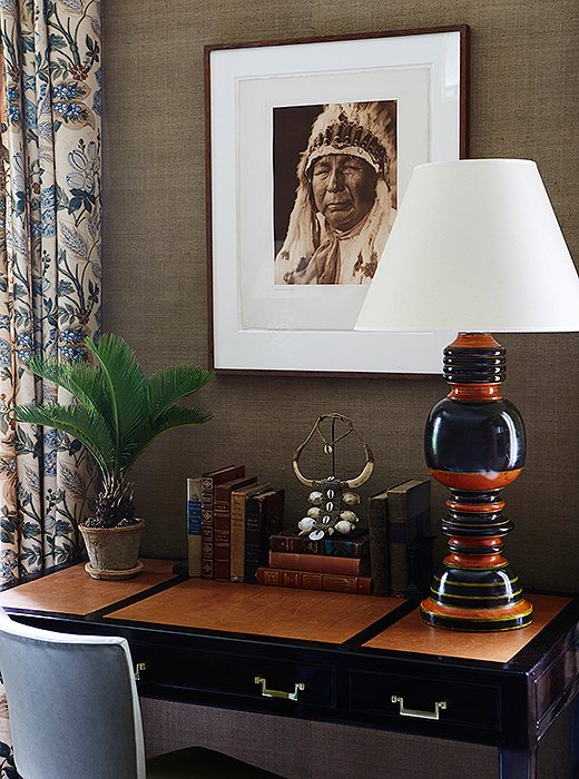The Indian balustrade lamp, topped with a crisp white shade, was found at John Rosselli Antiques, and the Native Americanprint is by Edward Curtis.