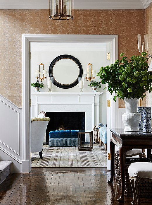 "The living room fireplace was painted to mimic ""a washed Carrara marble"" for a softer look, Suzanne tells us. The round mirror was painted black for vintage appeal; it's meant to complement the custom rectangular ottoman."