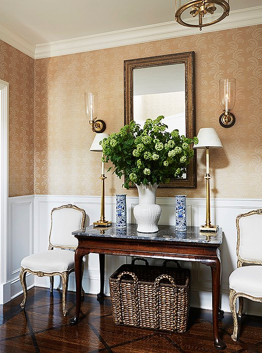 Pairs reign in the foyer, where antique chairs found in Connecticut flank an English marble-top console found at John Rosselli Antiques. Candlestick lamps by Visual Comfort add a modern glimmer.