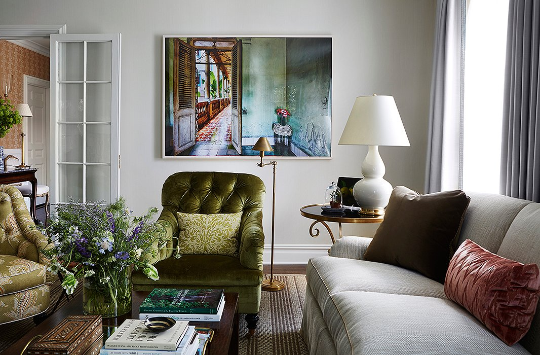 The McGraths opted for a modern photograph that brought a fresh perspective to the living room. The green silk velvet upholstery is by Schumacher, and the paisley is by Lee Jofa.