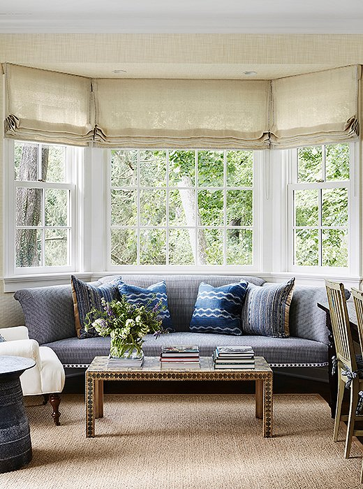 Shades of blue carry over into the home office, a family-friendly space that opens onto the patio, thus prompting thenatural-fiber rug and a metal outdoor side table. Thedecoupaged coffee table is vintage.