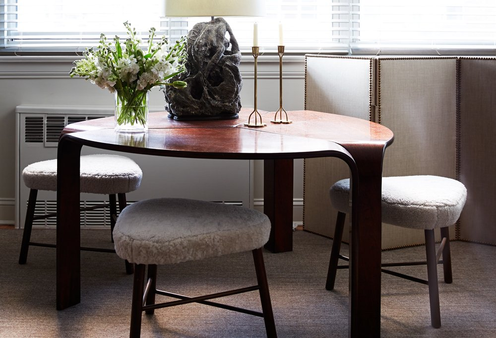 A lava-rock lamp, which is among his favorite pieces in the apartment, complements the dining table's sculptural shape.