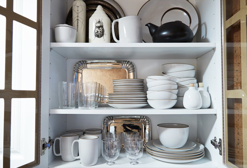 A glass-front kitchen cupboard brings to mind an old-fashioned butler's pantry and is filled with Shawn's everydaydishware.