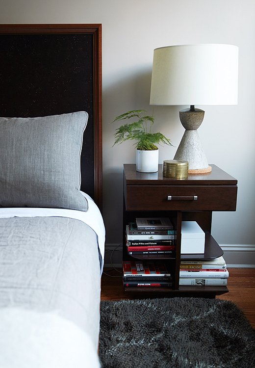 A conical concrete table lamp sits atop a book-filled nightstand with smart open shelves.