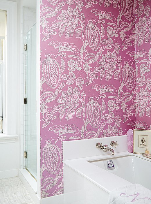 "To invigorate the all-white bath, Amanda covered the walls with a Manuel Canovas paper in hot pink. ""It's sort of my little nook when I'm relaxing at the end of the day,"" she says. ""It's my happy spot."""