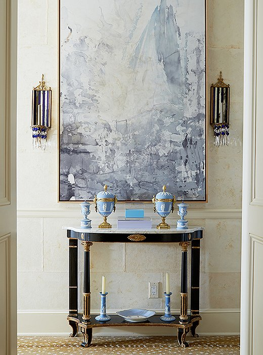 "The front hall showcases Amanda's intuitive touch for balancing old and new: A modern abstract by Ray Kass and flanking midcentury mirrored glass sconces command focus above a neoclassical-style console—""one of my first purchases,"" says Amanda. The antelope carpet is by Stark."