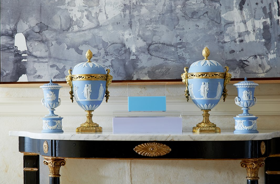 "Wedgwood vessels represent family history. ""They were my great-grandmother's,"" says Amanda. ""I love the juxtaposition of the color of the Wedgwood with the gold and the sculptural quality of the modern art."""