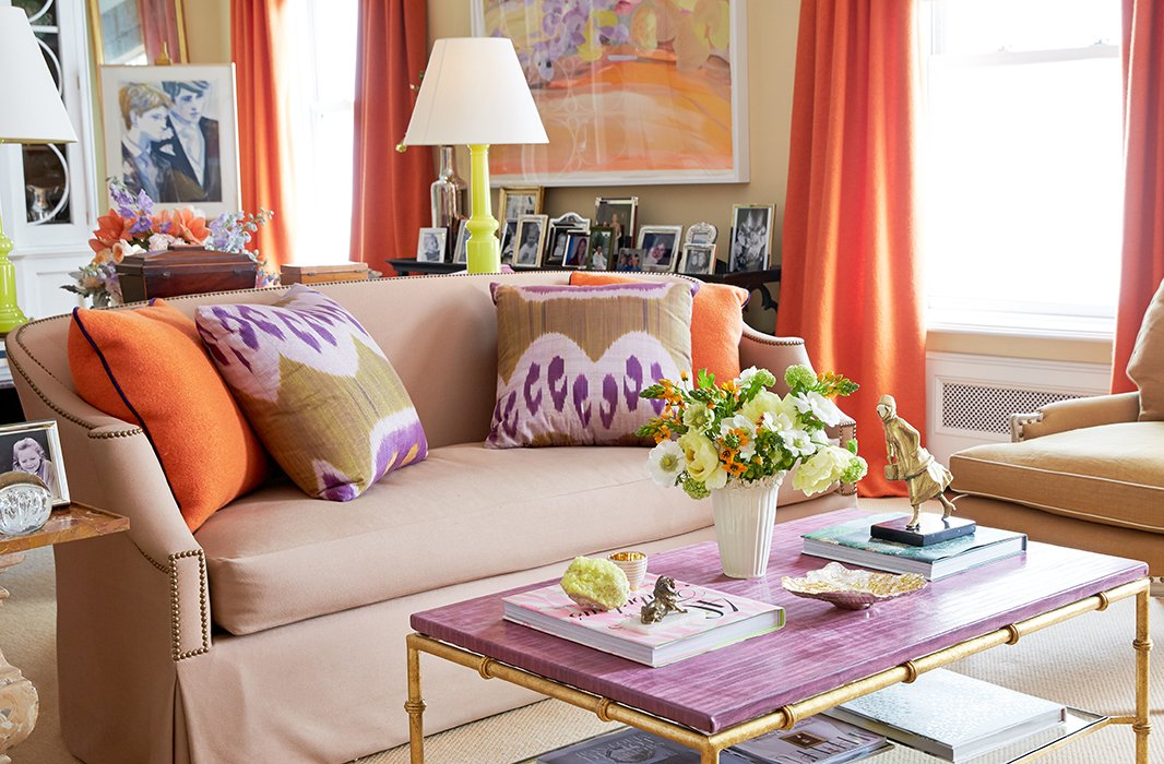 "Brilliant colors lead the way in the ever-changing living room (""It's a hazard of the profession""), starting with the punchy orange boiled wool by Holland & Sherry used on the curtains and pillows and the purple leather-top table designed by Amanda for Niermann Weeks."