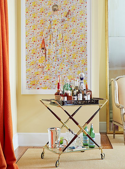 """I love that bar carts have come back into fashion,"" says Amanda, whose rosewood-and-brass bar is always ready for cocktail hour in her living room. Equally intoxicating is a large-scale photo by Rachel Perry Welty."