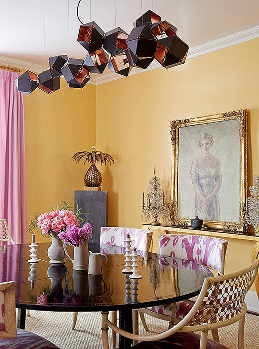 "A steel-and-copper light fixture by Gabriel Scott hangs above a painting of Amanda's maternal grandmother (""I like to think that she watches over all of my parties!"") and a black lacquered dining table surrounded with chairs she designed for Niermann Weeks."