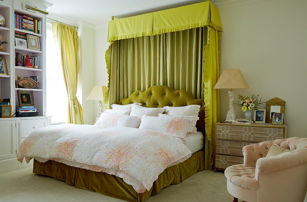 "The bedroom is Amanda's haven, although color finds its way inside. ""I believe in a soft palette for the bedroom, but I'm not one to do all white for myself,"" she says. The walls are painted in Farrow & Ball's Pointing, and the green bed curtains are made with Manuel Canovas and Fortuny fabrics."