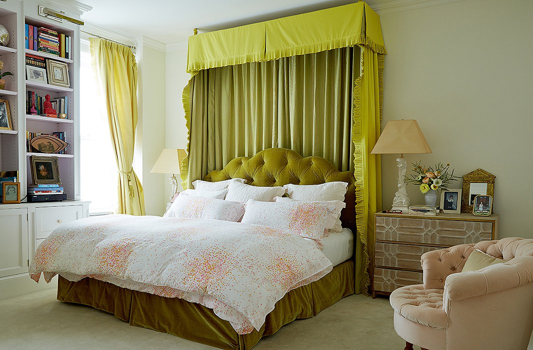 """The bedroom is Amanda's haven, although color finds its way inside. """"I believe in a soft palette for the bedroom, but I'm not one to do all white for myself,"""" she says. The walls arepainted in Farrow & Ball's Pointing, and thegreen bed curtains are made withManuel Canovas and Fortuny fabrics."""