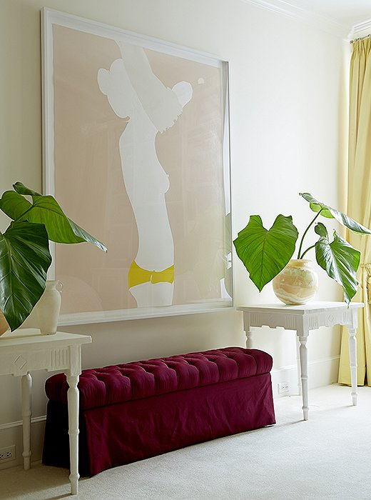 """I love the cheeky subject matter and her use of color,"" says Amanda of the nude painting by Natasha Law, which presides over her bedroom above a custom-made bench and tables by Brooklyn plaster artist Stephen Antonson."
