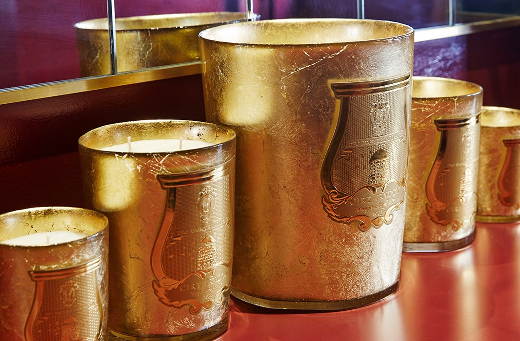 The gold-leaf vessels, handcrafted in Tuscany, are shaped likechampagne buckets. Cire Trudon's signaturecrest features a Latin inscription referencingthe bees' work for God and King Louis XIV.