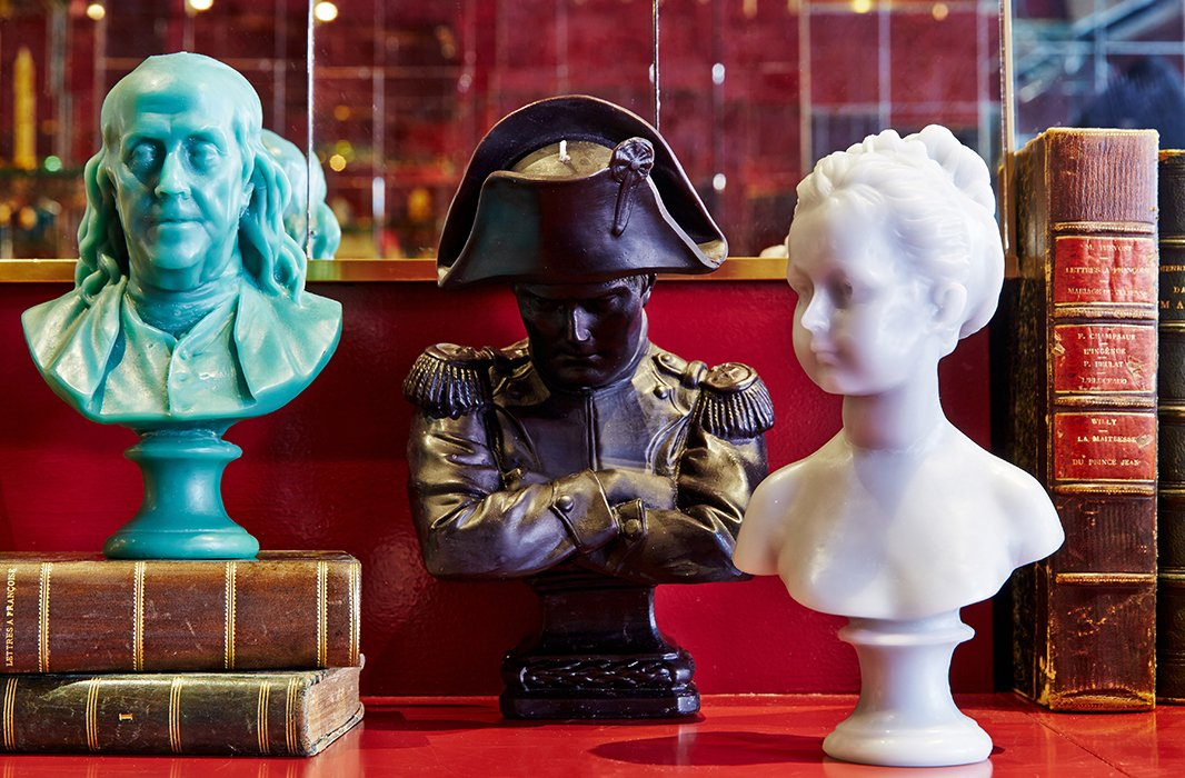 Cire Trudon's nonscented wax candles include busts sculpted in the form of renowned figures such as Napoleon Bonaparte. Vintage books by famous French authors, from Voltaire to Camus, makeaptly refined decor.