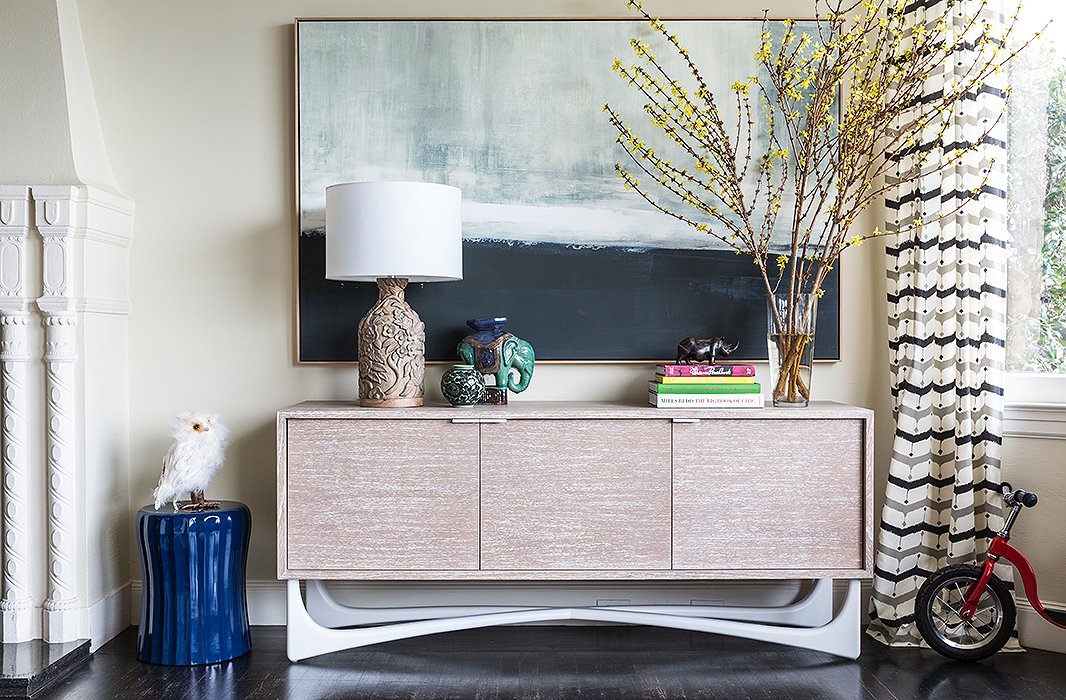 A corner captures the couple's flair for eclectic vignettes. Here, a painting by Carol Benson Cobb is displayed withaSelamat stool and sideboard; the glazed ceramic elephant was a gift.