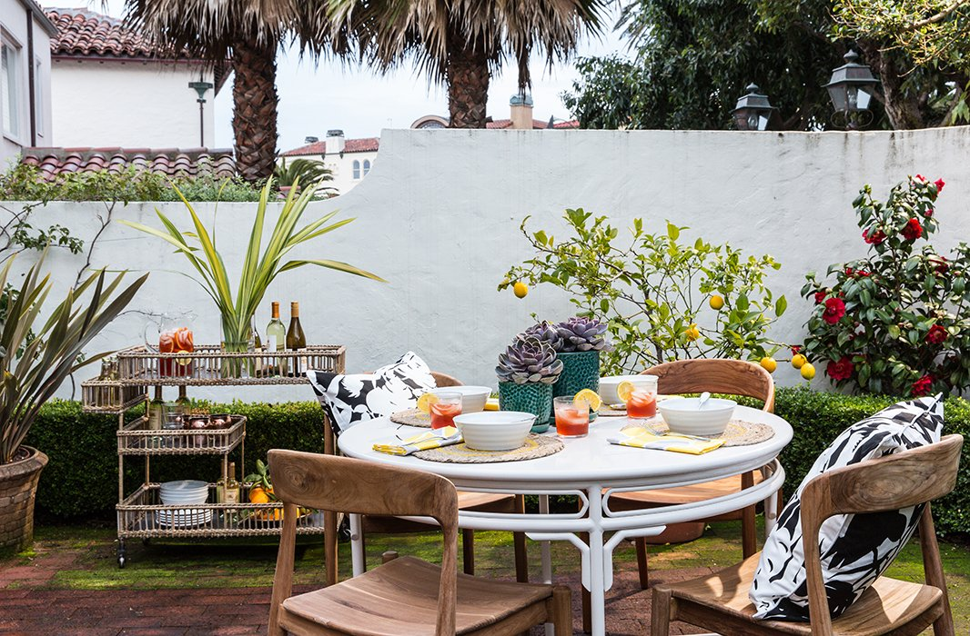 The family's favorite gathering spot, the backyard, gets beautiful morning light and is planted with lemon trees and a camellia bush. It's always entertaining-ready with a dining set and bar cart designed by the couple.