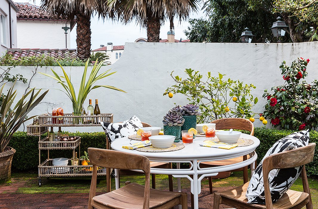 The family's favorite gathering spot, the backyard, gets beautiful morning light and is planted with lemon trees and a camellia bush. It's always entertaining-readywith a dining set and bar cart designed by the couple.