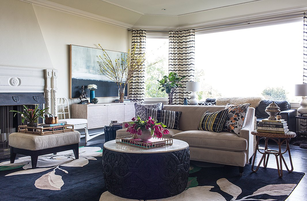 """""""We love mixing materials in our designs,"""" says Shannon of themarble-and-carved-wood ottoman depicting Broadhurst's Fruit Vine pattern. The pillows are also from Selamat'sBroadhurst line; therug is by Vivienne Westwood forThe Rug Company."""