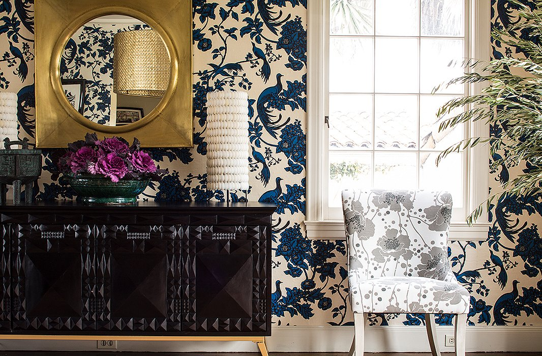 """A chair in a Broadhurst floral is paired with asculptural consolethatmimics one of the designer's geometrics. """"It's completely changed the feel of our dining room to add a really dark color,"""" says Shannon. """"It's made the room feel richer whileserving the same function."""""""