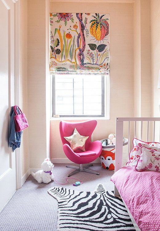 A Roman shade crafted from Josef Frank fabric hangs over a sleek, baby-size egg chair in youngest daughter Daisy's room.