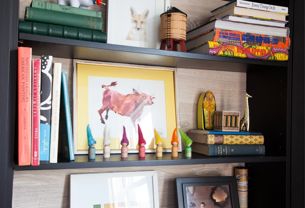 Favorite books, curios, and pieces of art, including a baby fox print from The Animal Print Shop, share space on Lilly's dining-room bookcase.