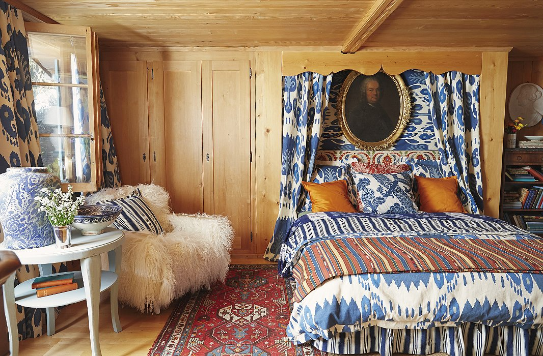 Stripes, ikats, and florals—all in a bold mix of blue and orange—coexist happily in the Gstaad bedroom of one of Michelle's sons. Solid orange throw pillows and a plush sheepskin chair give the eye a moment to rest.
