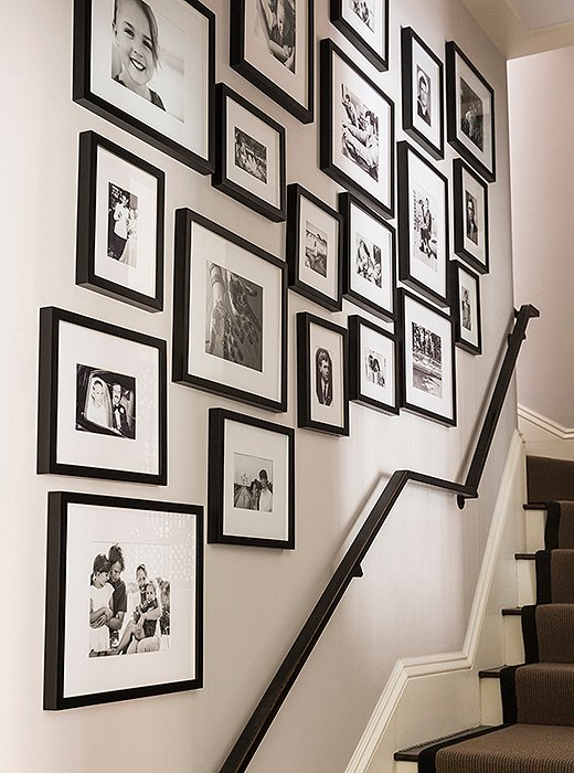 "Black-and-white family portraits line the stairwell, leading the way up to the second floor. ""We collect it from our family—vintage photos of them, my parents' wedding picture, the kids throughout. You never can have enough picture space,"" says Nina."