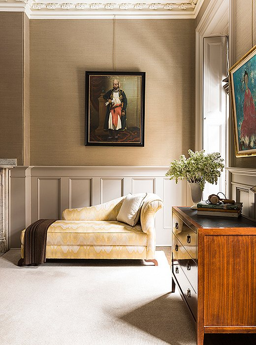 "In a corner of the master bedroom sits Nina's most prized possession. ""The chaise is actually the first piece of furniture that I ever bought on my own after college,"" says Nina of the Fendi piece, which she reupholstered in a yellow-stitch fabric. ""It's traveled with me all this time."" The vintage painting of a maharaja is from Jaipur, India."