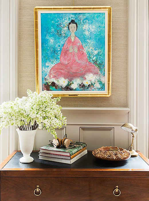 A painting that Nina and her husband discovered abroad hangs above a chest of drawers holding books, magazines, and Nina's keepsakes. A wooden bowl by Nina's father makes an elegant catchall for her jewelry.