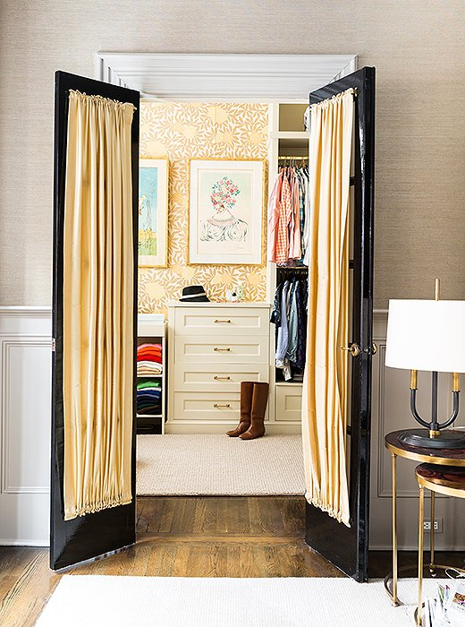 Plaster moldings and doors painted in a Fine Paints of Europe high-gloss black frame the entrance to the spacious walk-in closet, which was once a nursery for Nina's daughter.