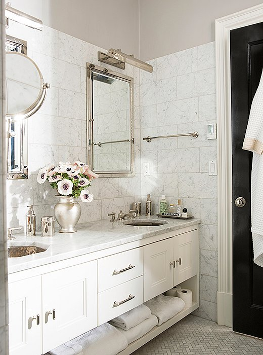 Originally the second-floor kitchen, the master bath was revamped with honed Carrara marble wall tiles, gleaming fixtures, and octagonal sinks, a nod to the home's architectural elements one floor below. The walls are painted in Benjamin Moore Aura.