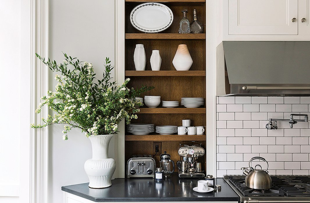 Nina kept all the shelving open to take advantage ofthe high ceilings whileserving as gorgeous displays. Here, her collection of white Nymphenburg vesselsandan Hermès plattercomplement thesculptural vase from Aero on the counter.
