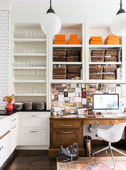 """""""I like keeping an eye on what's happening in the house yet having my own space off the kitchen,"""" says Nina of her built-in office area,organizedwith fabric swatches, paint chips, and inspirations."""