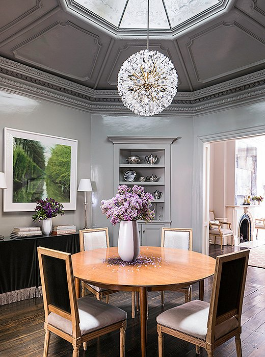 "The formal dining room, with its beautiful 12-feet-high octagonal ceiling, is also the home's grand entry. ""We can fit 10 to 12 people in here,"" says Nina of the leaf table. The high-gloss walls are painted with Farrow & Ball's Lamp Room Gray. The Lynn Geesaman photo was Nina and her husband's first art purchase together."